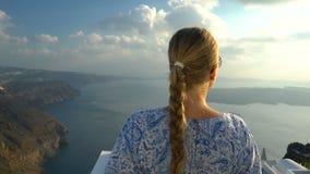 白色和蓝色礼服的愉快的妇女享受她的在圣托里尼,希腊的假日 在破火山口和爱琴海的看法从 股票录像