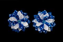白色和蓝色缎丝带和水晶的弓 查出在黑色背景 库存图片
