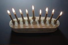 白色和金子光明节menorah的顶上的看法与被点燃的蜡烛 图库摄影