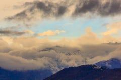 白色和黑暗的云彩围拢的一座多雪的山 库存照片