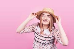 白色和黑条纹的,帽子,太阳镜可爱的女孩,情感地张了在明亮的桃红色背景的嘴与 免版税库存图片