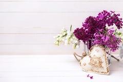 白色和紫罗兰色淡紫色花和装饰心脏在白色p 库存图片