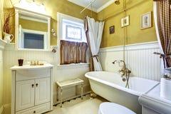 白色和黄色古色古香的卫生间内部 库存照片