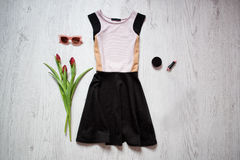白色和黑色穿戴,郁金香,太阳镜,唇膏 秀丽蓝色聪慧的概念表面方式构成妇女 春天衣橱 木背景 免版税库存图片