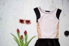 白色和黑色穿戴,郁金香,太阳镜 秀丽蓝色聪慧的概念表面方式构成妇女 春天衣橱 木背景 图库摄影