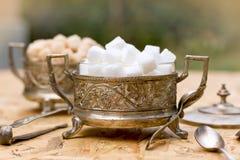 白色和黄色糖(立方体)在银色容器-古色古香的碗 免版税库存图片