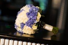 白色和紫色花婚礼花束在桌上的 免版税库存图片