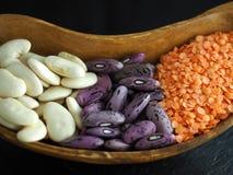 白色和紫色豆用在一个木碗的红色小扁豆 免版税库存图片