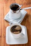 白色咖啡与烹调罐的在桌上 免版税库存图片