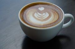 白色咖啡与美好的拿铁艺术的在黑背景 免版税库存图片