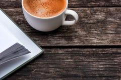 白色咖啡和一本书在木桌上 库存图片