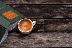 白色咖啡和一本书在木桌上 免版税图库摄影