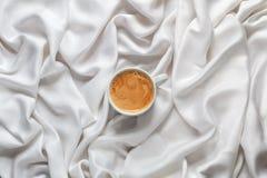 白色咖啡在一件白色丝织物的 浓咖啡有泡沫的咖啡杯以兴高采烈的面孔的形式 图库摄影