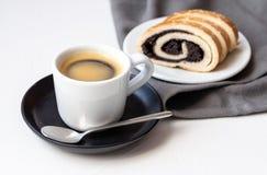 白色咖啡在黑茶碟垫的有后边罂粟种子蛋糕的 库存图片