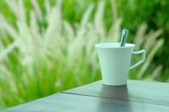 白色咖啡有自然绿草背景 免版税图库摄影