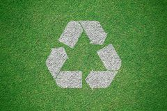 白色回收在从顶视图的绿草领域绘的商标 r 图库摄影