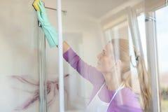 白色围裙清洗的玻璃阵雨客舱的年轻美丽的妇女 免版税库存图片