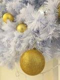 白色圣诞节树装饰关闭了闪烁金黄球装饰品有白色闪亮金属片背景 免版税图库摄影