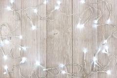白色圣诞节点燃在浅灰色的木头的框架 免版税库存图片