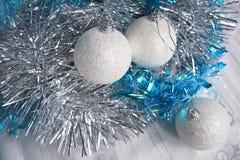 白色圣诞节球和闪亮金属片在桌布 免版税库存照片