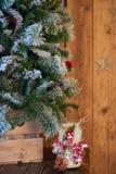 白色圣诞节用杉木锥体和ashberry棍子装饰的蜡烛台在木背景的圣诞树下与星 免版税库存图片