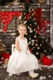 白色圣诞节礼服的逗人喜爱的年轻美丽的女孩 免版税图库摄影