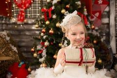 白色圣诞节礼服的逗人喜爱的年轻美丽的女孩 免版税库存图片