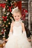 白色圣诞节礼服的逗人喜爱的年轻美丽的女孩 库存图片