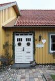白色圣诞节装饰了在黄色房子墙壁的门 免版税库存照片