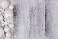 白色圣诞节装饰品与雪的边边界在白色木头 库存图片