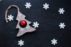 白色圣诞节雪花装饰和木圣诞节在黑织地不很细背景戏弄 免版税库存照片