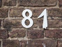白色在一个老砖墙上的房子号码81 免版税库存图片
