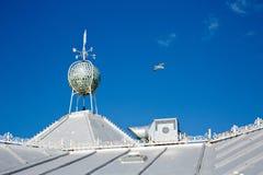 白色在一个晴天cladded有一面试风旗的屋顶在屋顶 免版税库存照片