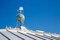 白色在一个晴天cladded有一面试风旗的屋顶在屋顶 库存照片