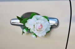 白色在一辆汽车的把柄的玫瑰花在婚礼之日 库存照片