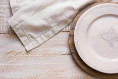 白色在圆的切板,在白色木背景,普罗旺斯样式的亚麻布的葡萄酒空的板材 免版税库存照片