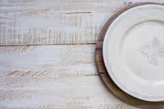 白色在圆的切板,白色板条木背景,普罗旺斯样式的葡萄酒空的板材 免版税库存照片