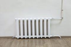 白色在墙壁上的铁幅射器中央系统暖气在屋子里 免版税库存照片