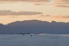 白色在日落、山和人剪影的沙子国家历史文物 免版税库存照片