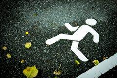 白色在沥青的被绘的标志 步行车道和黄色烘干叶子 图库摄影