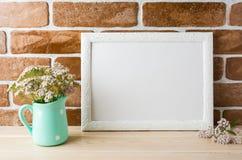 白色在薄荷的投手的风景框架大模型乳脂状的桃红色花 免版税库存照片