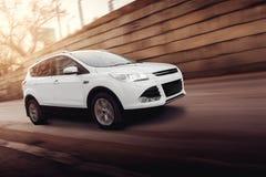 白色在路的汽车快速的驱动在城市 免版税库存照片