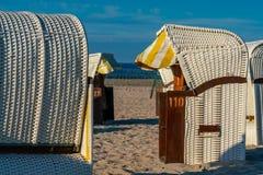 白色在金黄阳光下顶房顶了柳条海滩睡椅 免版税图库摄影