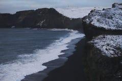 白色在黑沙子的波浪通过海岸和山 免版税库存图片