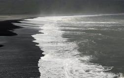 白色在黑海滩挥动 免版税库存照片