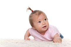 白色地毯的逗人喜爱的婴儿女孩 免版税库存图片
