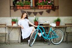 白色坐外面在舒适咖啡馆区域的礼服和草帽的可爱的女性在她的蓝色葡萄酒自行车旁边 免版税图库摄影