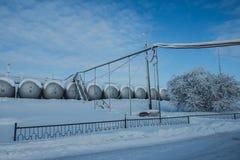 白色坦克在有铁楼梯的油库在雪 库存图片