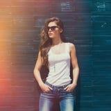 白色坦克衬衣太阳镜和蓝色牛仔裤室外夏日倾斜的女孩在铺磁砖的墙壁上 图库摄影