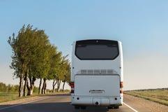 白色城市间的公共汽车沿路驾驶 免版税库存图片